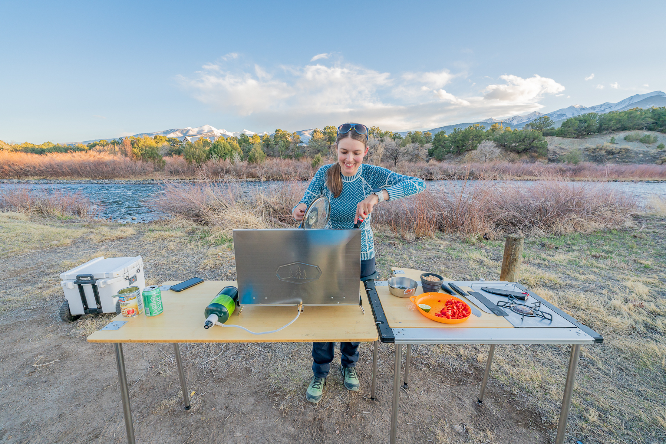the author cooking on the GSI pinnacle stove and stirring food on a large camp table at basecamp