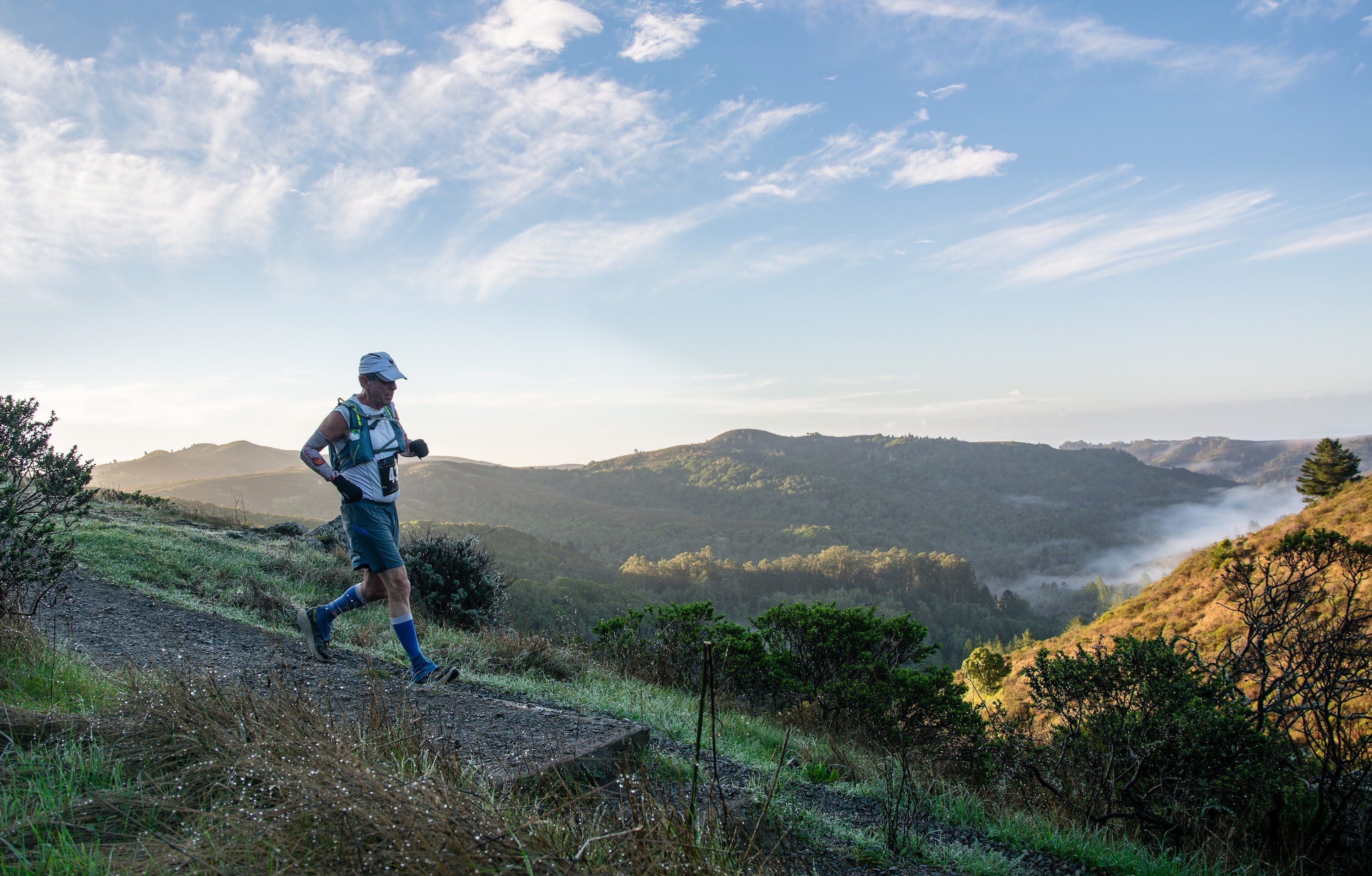 eric spector running down wide gravel trail with mountain overlook