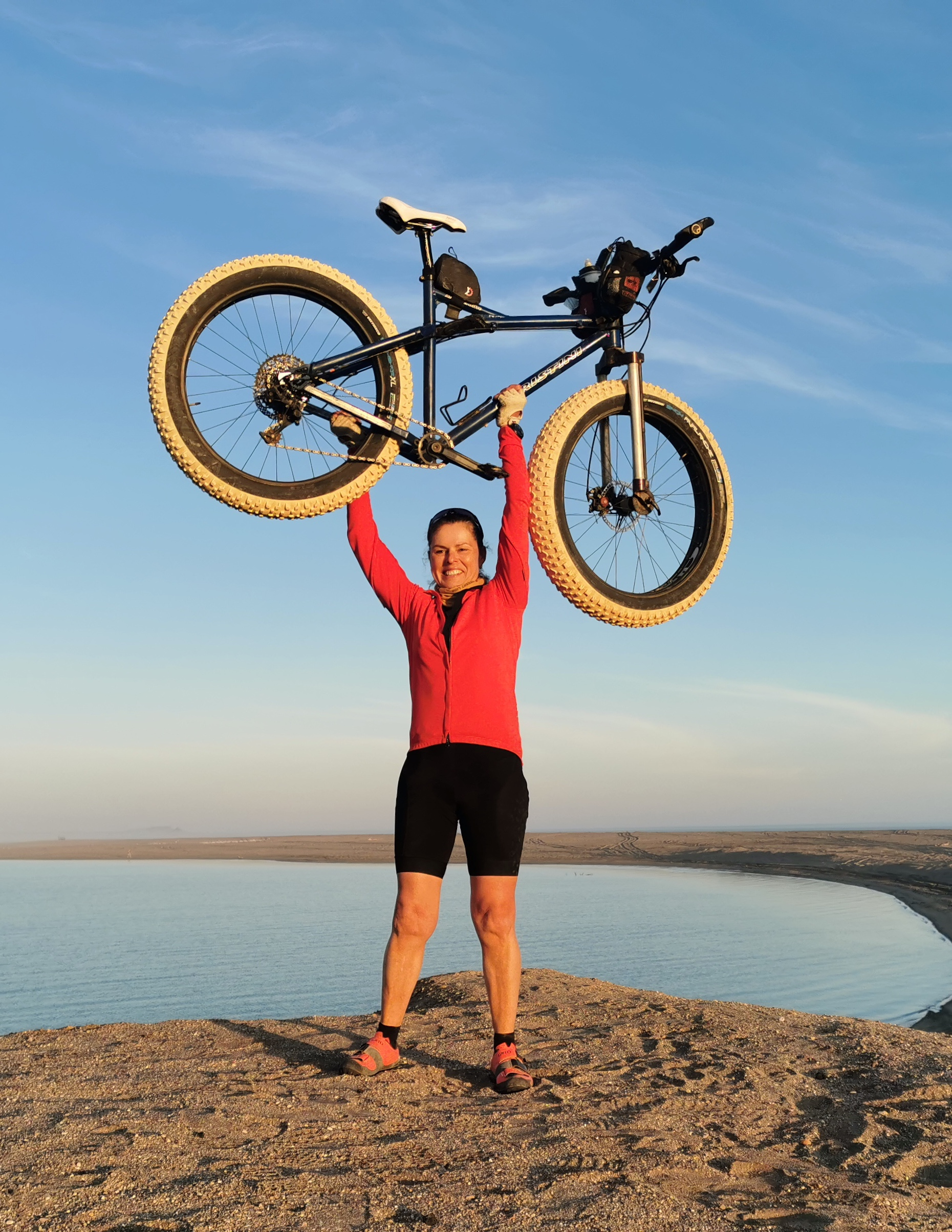 Kate Lemming holds up her fat bike in the desert