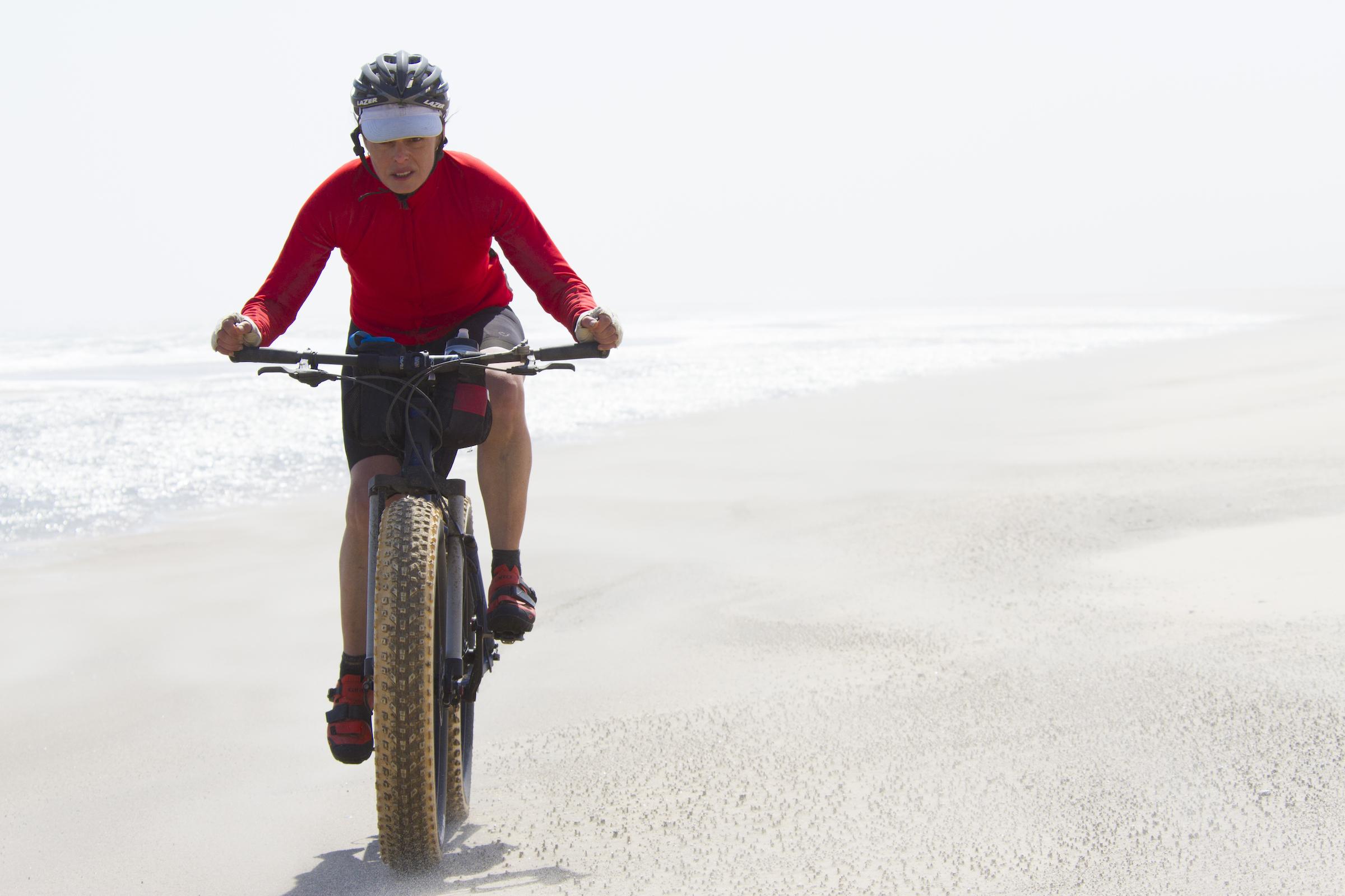 kate lemming cycling across hot white desert sand on a fat bike