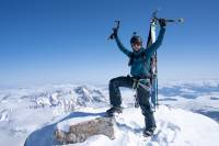 santi vega standing on the summit of the grand teton with ice axe in the air