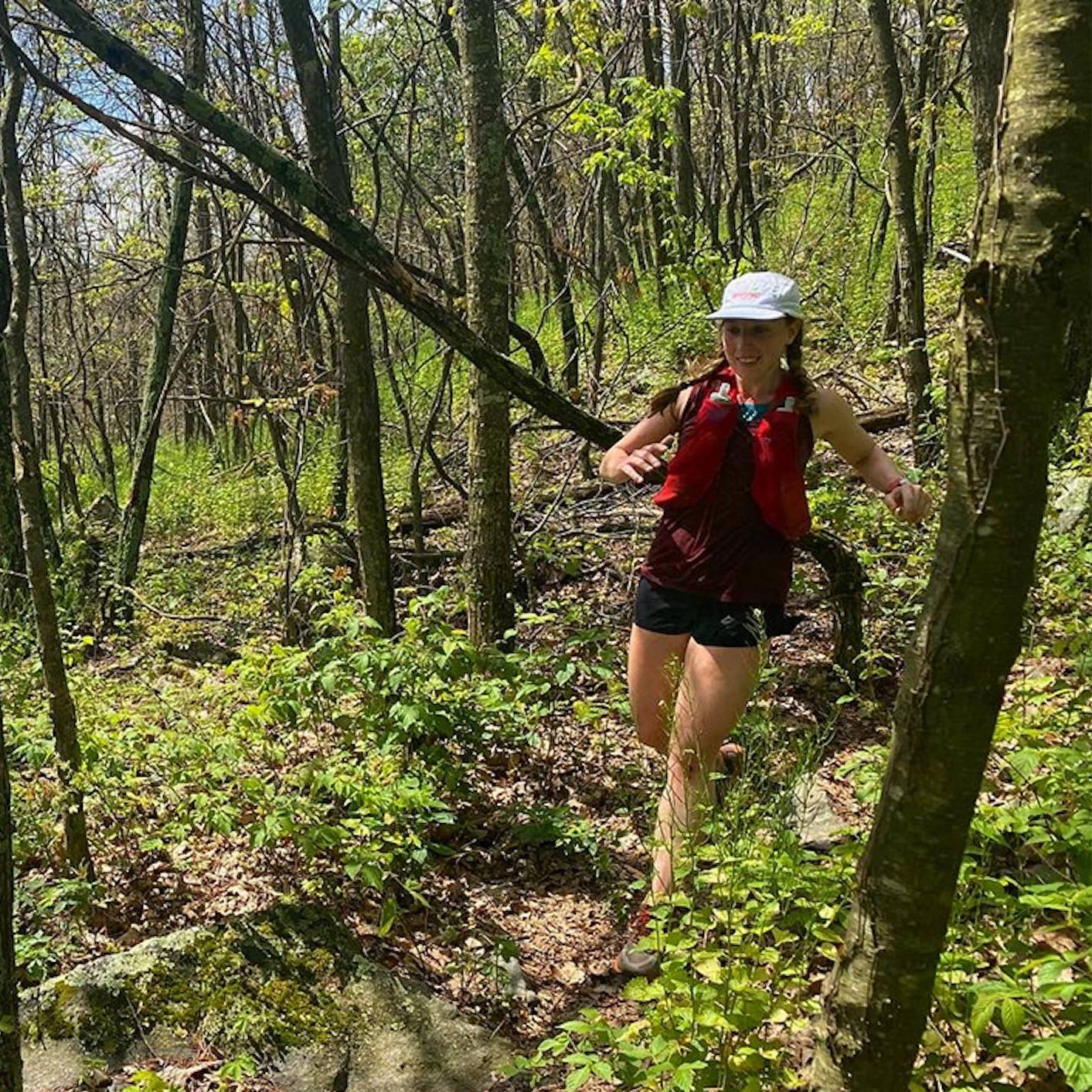 Sarah Hodder trail running through forest on sunny day