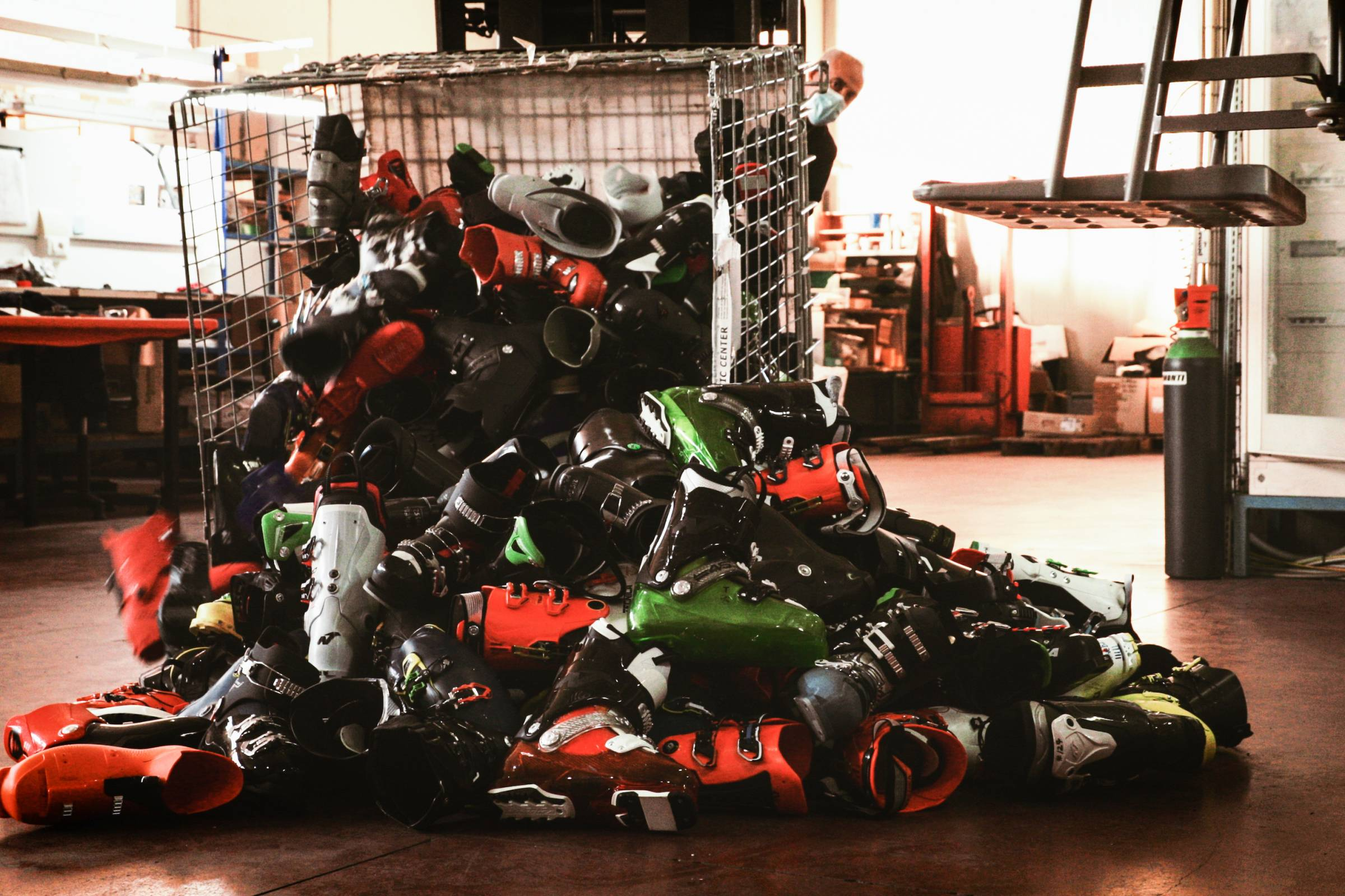 metal bin tipped over with Tecnica ski boots spilling out onto the floor