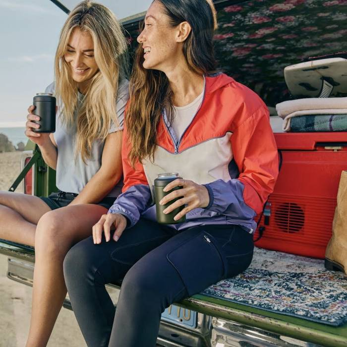 Two women sitting on trunk bed with cooler wearing Wrangler pants and apparel
