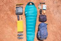 Bird's eye view of a female camper in a sleeping bag, surrounded by equipment on desert floor