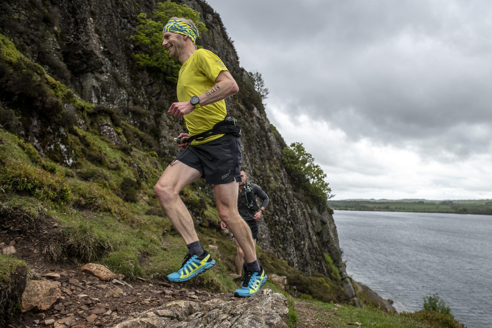 Damian Hall loopt een rotsachtig pad op en glimlacht