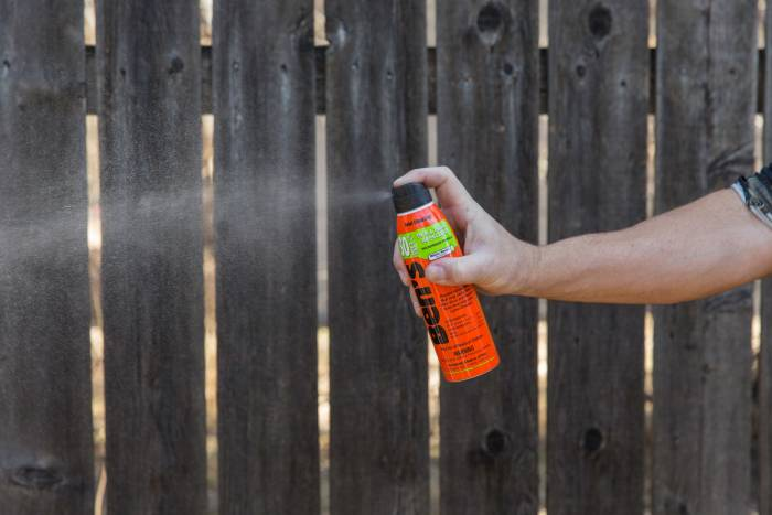 Ben's 30 6oz - arm holding and spraying, wooden fence background2