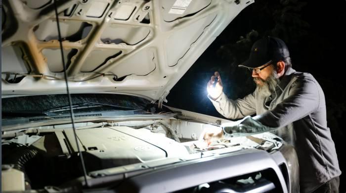 Fenix E12 EDC Flashlight under the hood of truck