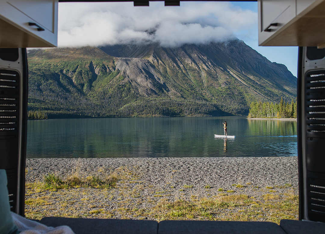 view from the back of an RV overlooking a paddleboarder on a lake and mountains