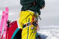 Petzl Fly Harness on a male skier in yellow shell pants