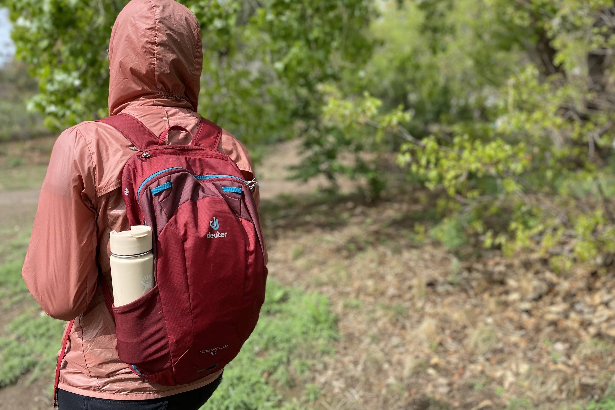 the author in a pink shell with a Deuter daypack hiking along a trail