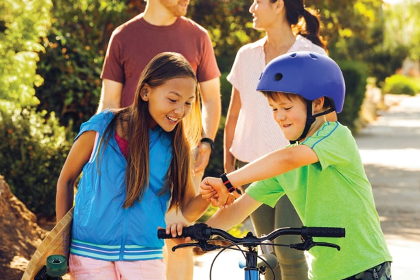 kids looking at boy's fitness tracker