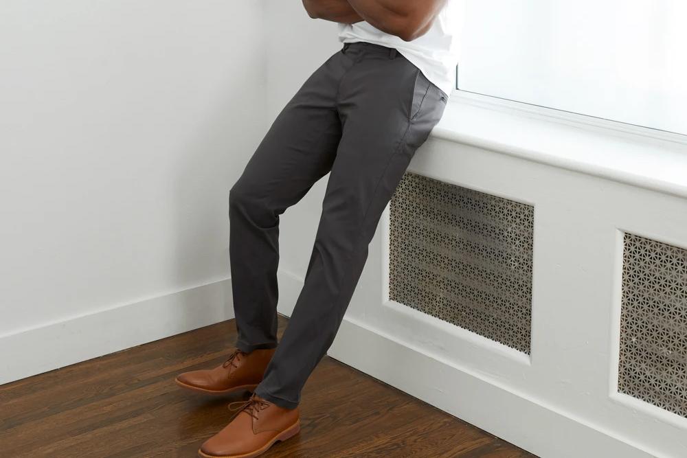 man wearing travel pants leaning on window ledge