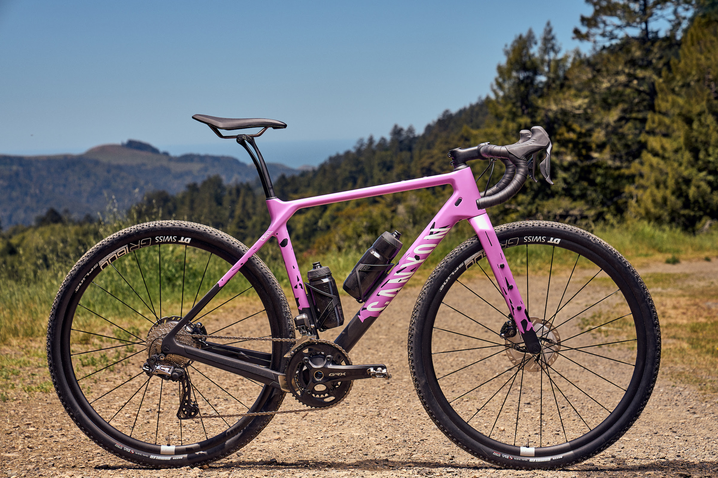 neon pink and crisp new Canyon Grizl gravel bike on dirt and gravel trail
