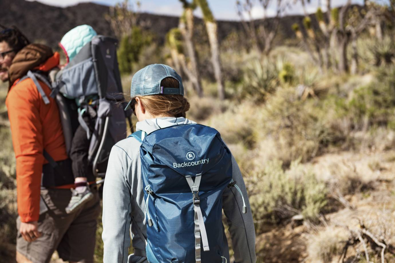 woman with blue pack and man with child carrier hiking in desert