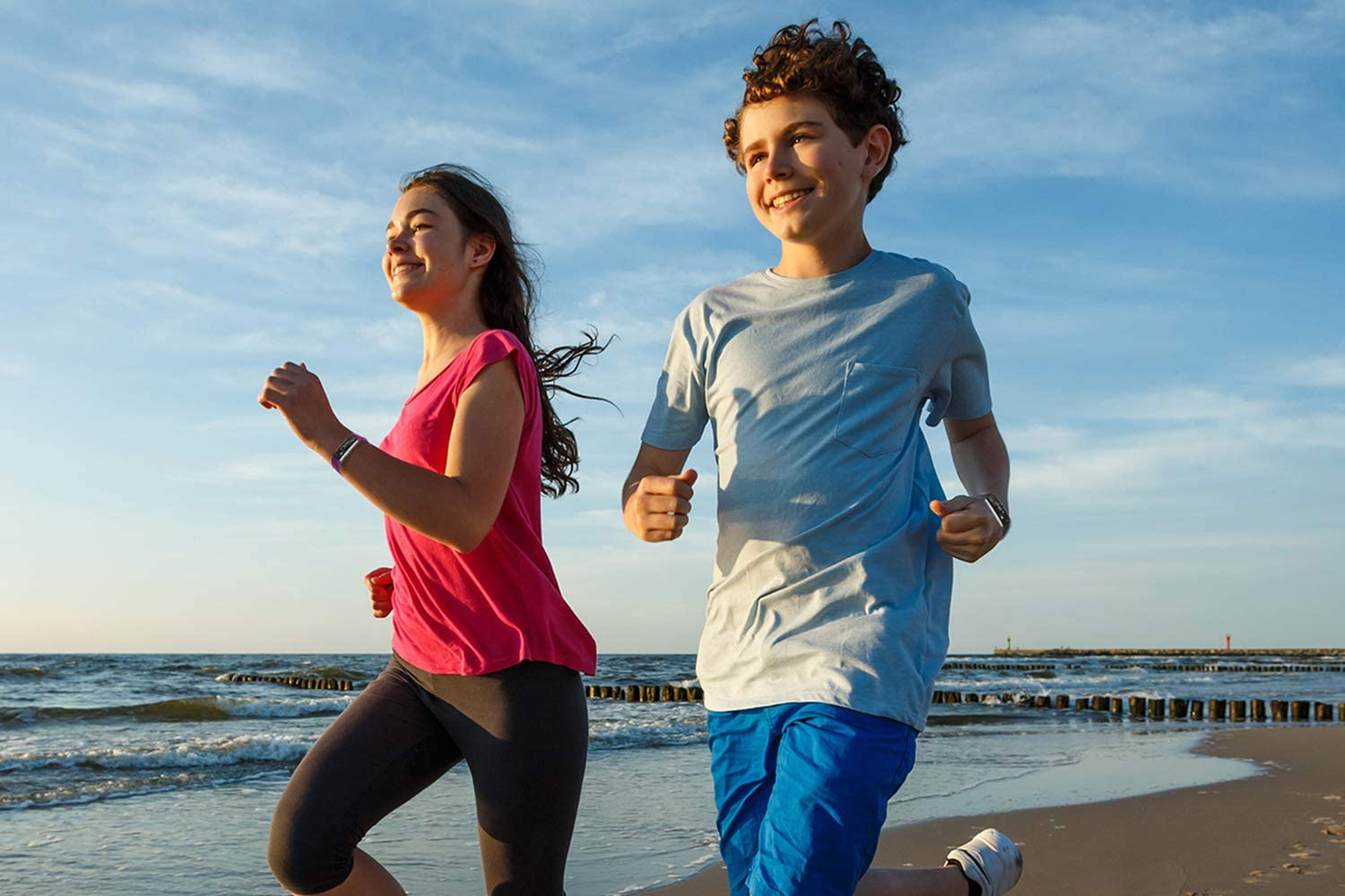 2 kids running with fitness trackers on the beach