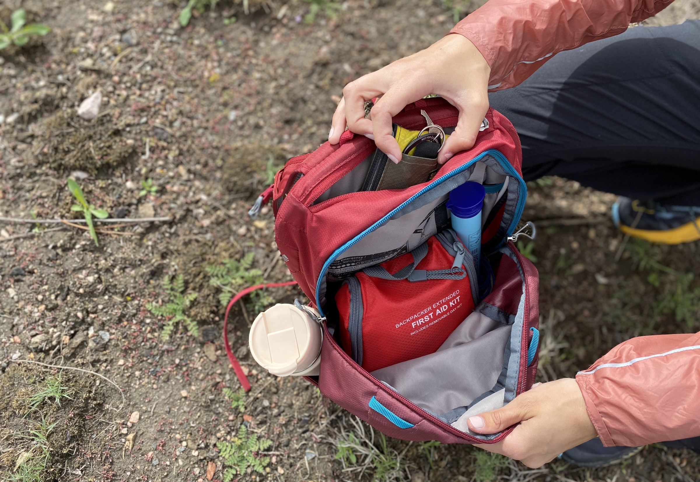 a red daypack with a first aid kit, layer, water bottle, and wallet visible