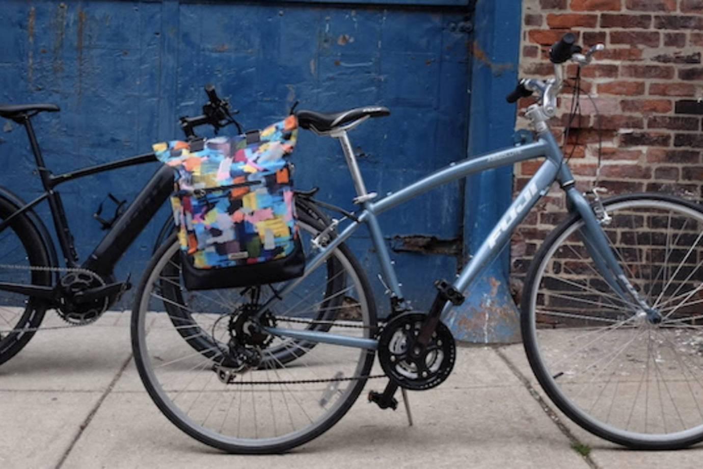 colorful pannier bike bag on women's cruiser by a blue brick wall