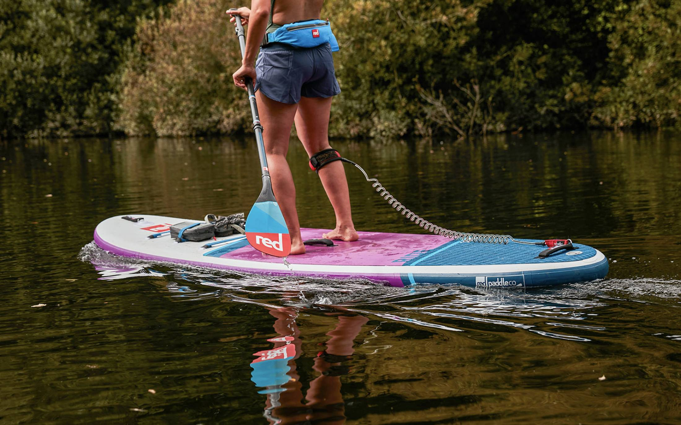 woman in shorts from waist down paddling red and pink board on flatwater