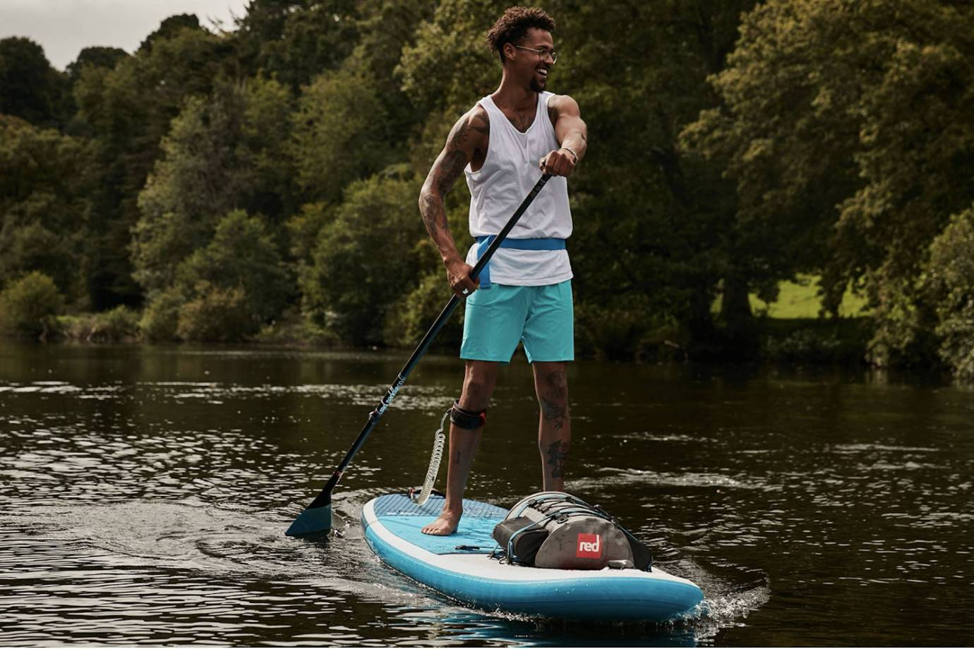 African American man in teal boardshorts paddleboarding on flatwater