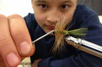 Young male child learns how to tie a fly for fishing