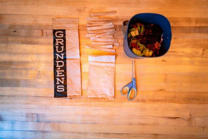 Compostable poly bags with the Grundéns' logo next to a home compost bin on a wooden table