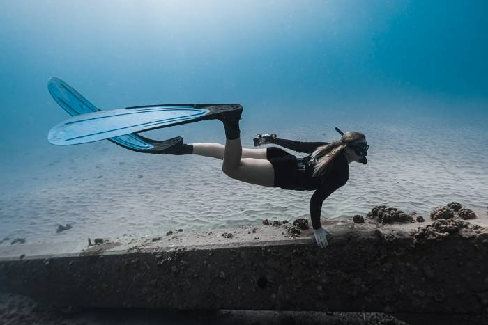 freediver along concrete underwater