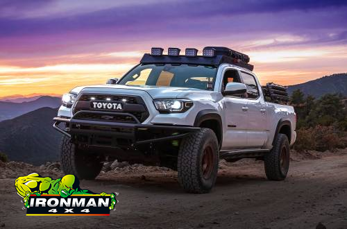 Toyota Tacoma with lift at sunset.