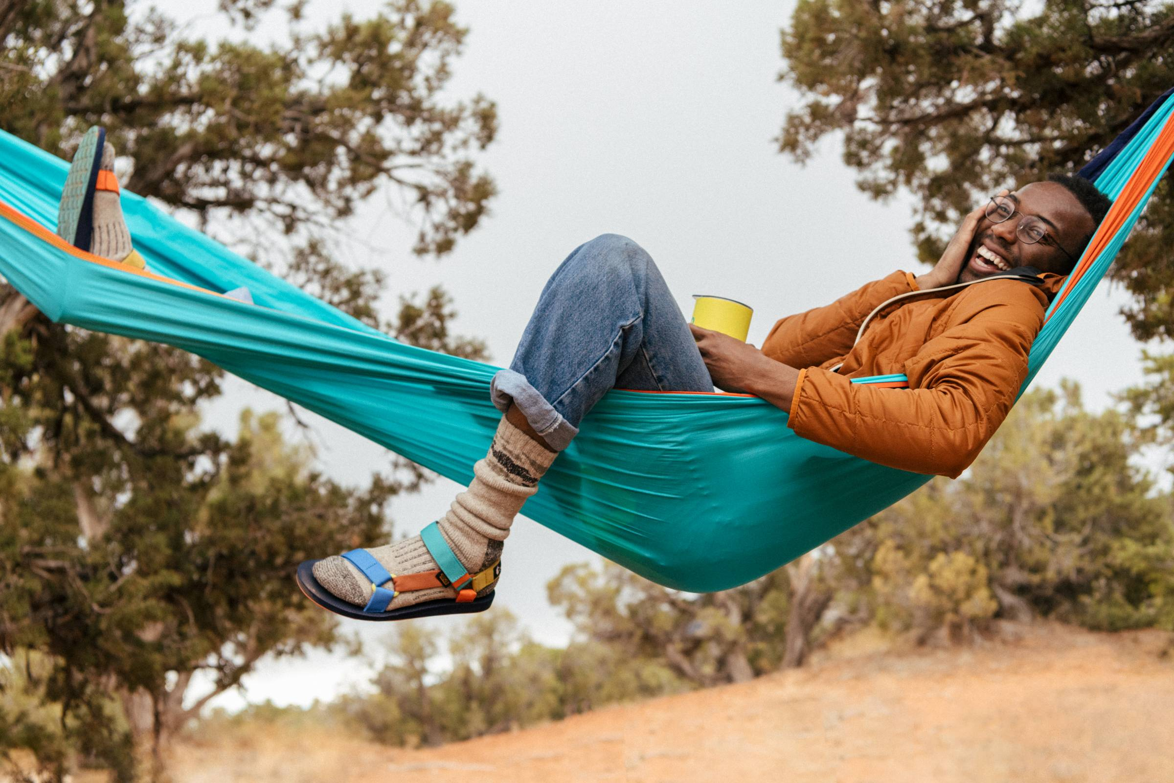 Black man lounging in ENO hammock in Cotopaxi and Teva sandals and gear