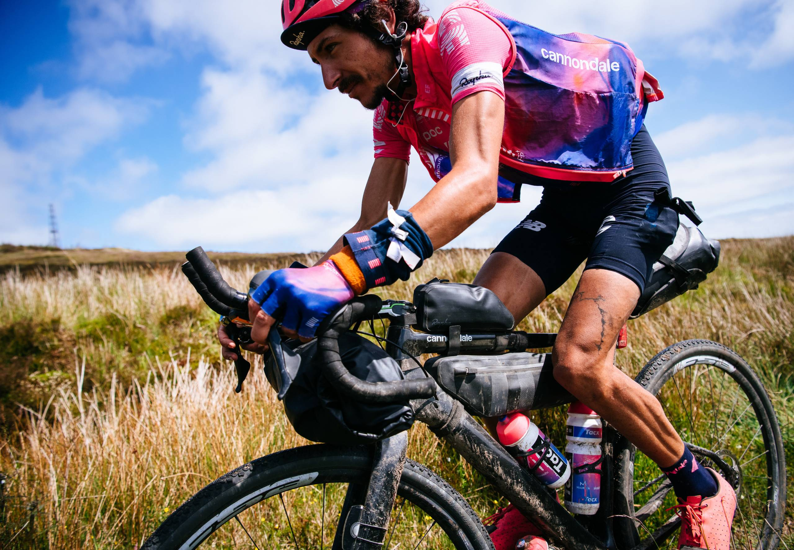 Lachlan Morton cycling in hot pink jersey, helmet with lots of gear strapped to his road bike