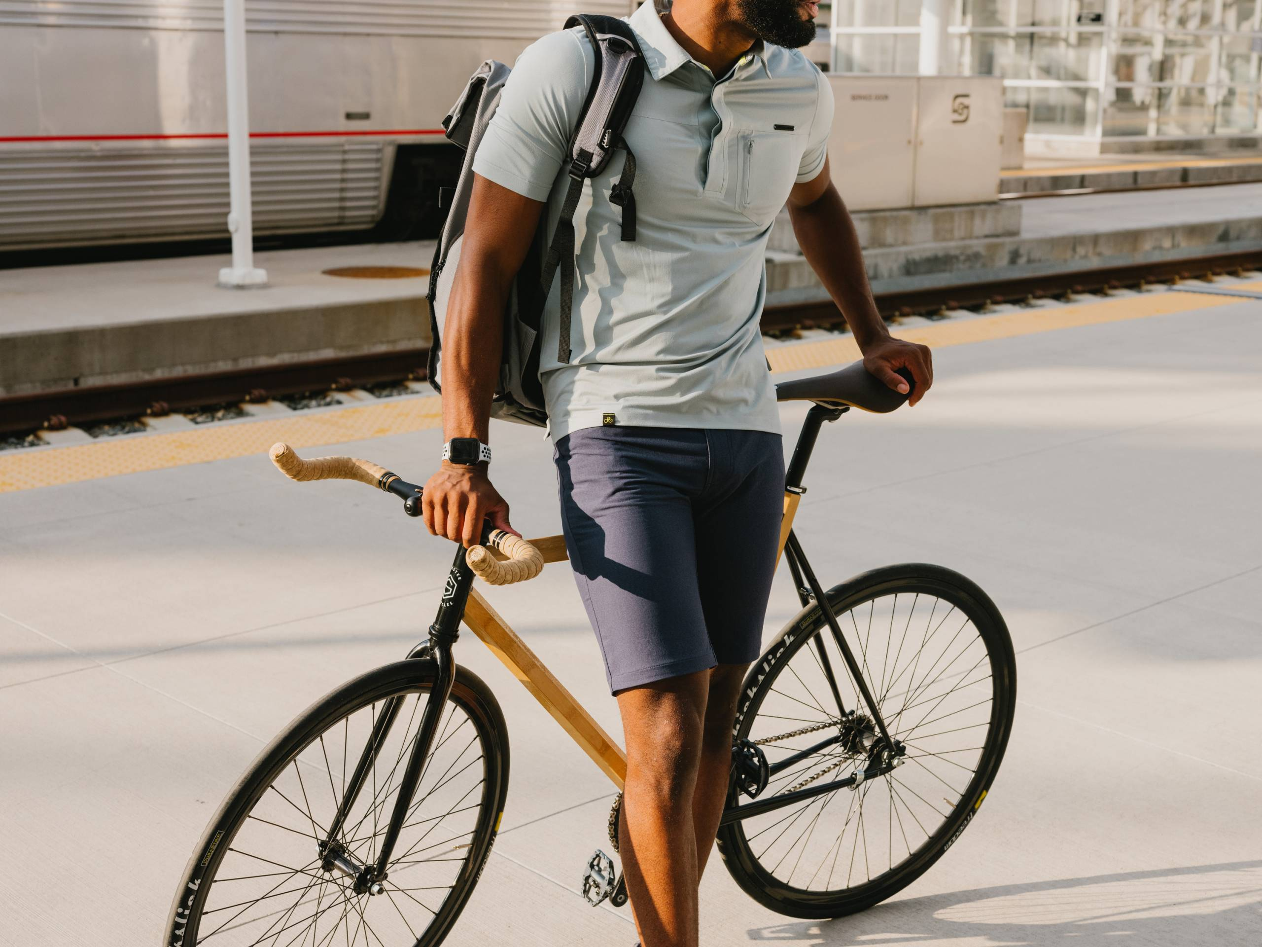 Black man from neck down in collared shirt and navy shorts leaning on his bike