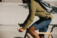 man in olive shirt jacket and navy shorts riding bike