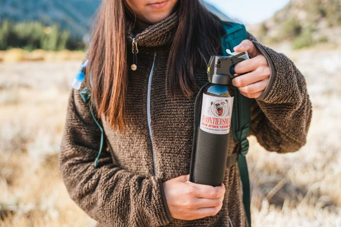 Woman holding SABRE Frontiersman Bear Spray canister