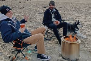 Two People On The Beach With Solo Stove Firepit
