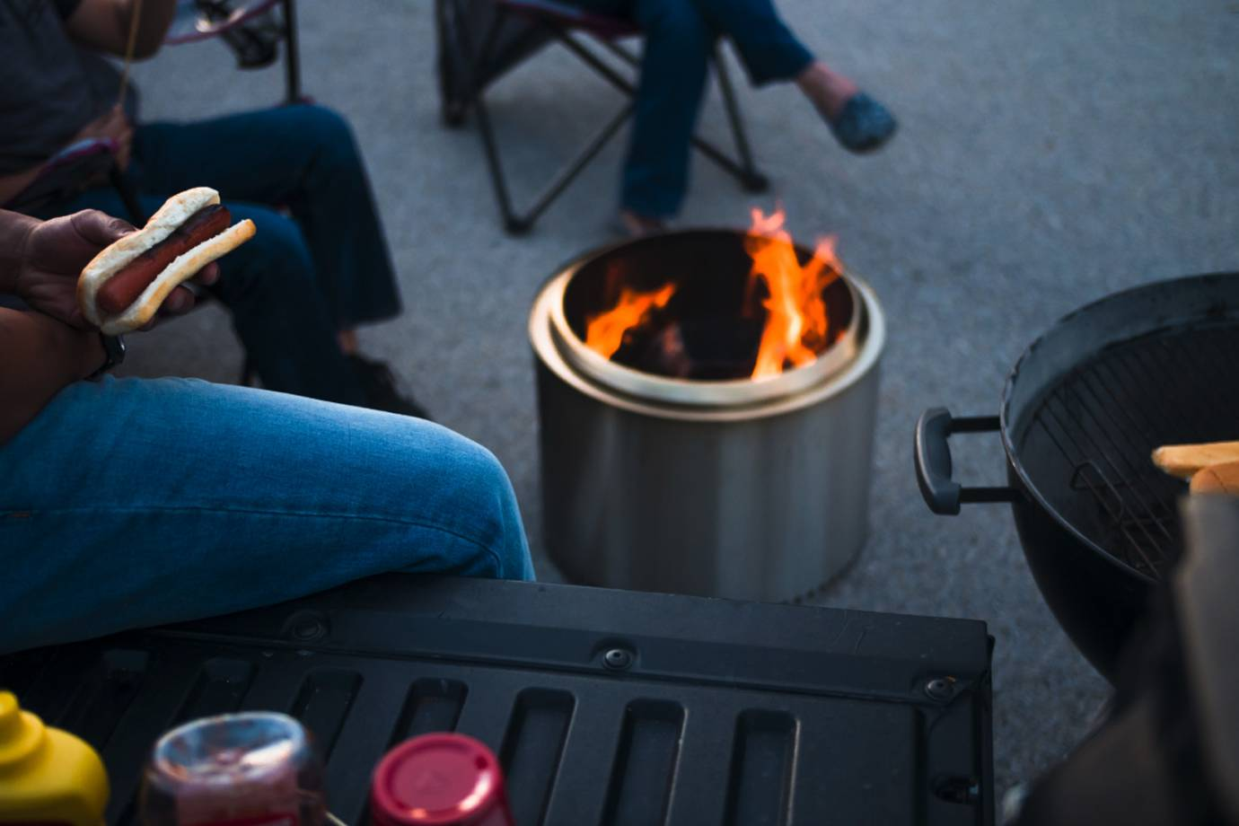 People sitting around solo stove fire pit eating