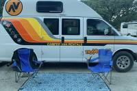 A rental campervan with outdoor blanket and camp chairs outdoors