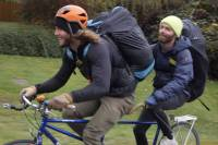 two men with duffel backpacks on a tandem bike