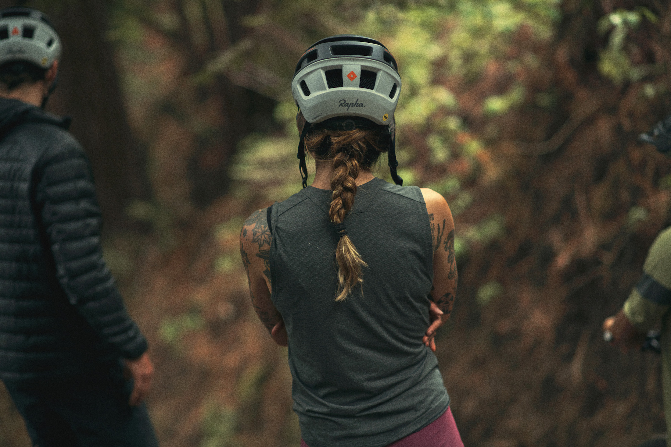 female mountain biker in a tank and helmet with her back turned to the camera
