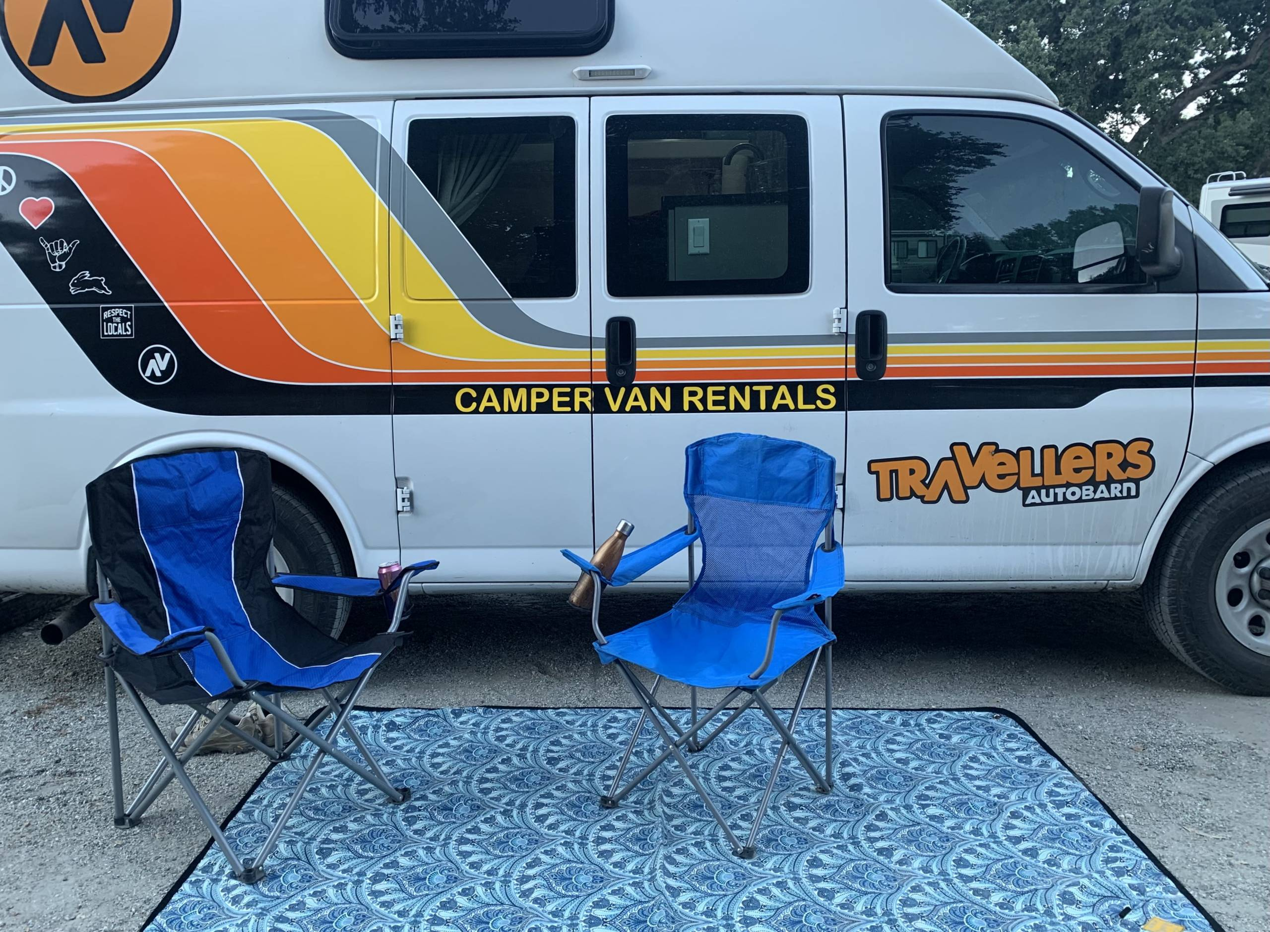 Travellers Autobarn campervan at camp with camp chairs and a blanket outdoors