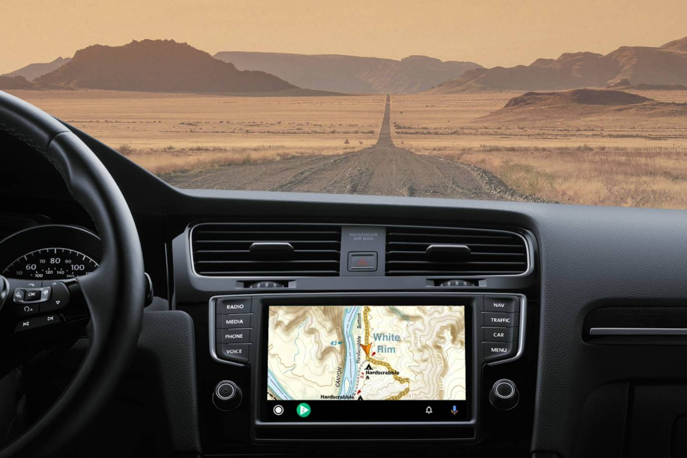 Gaia GPS app on screen dash in car looking out on desert back road