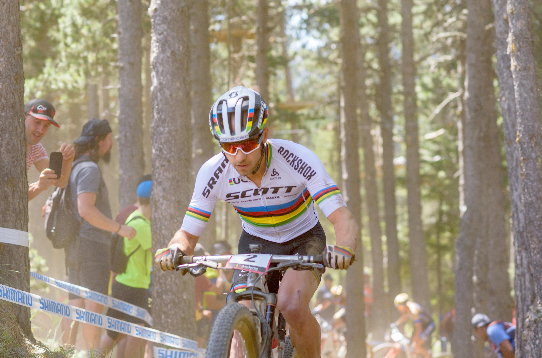 Swiss cyclist Nino Schurter climbing uphill on a mountain bike