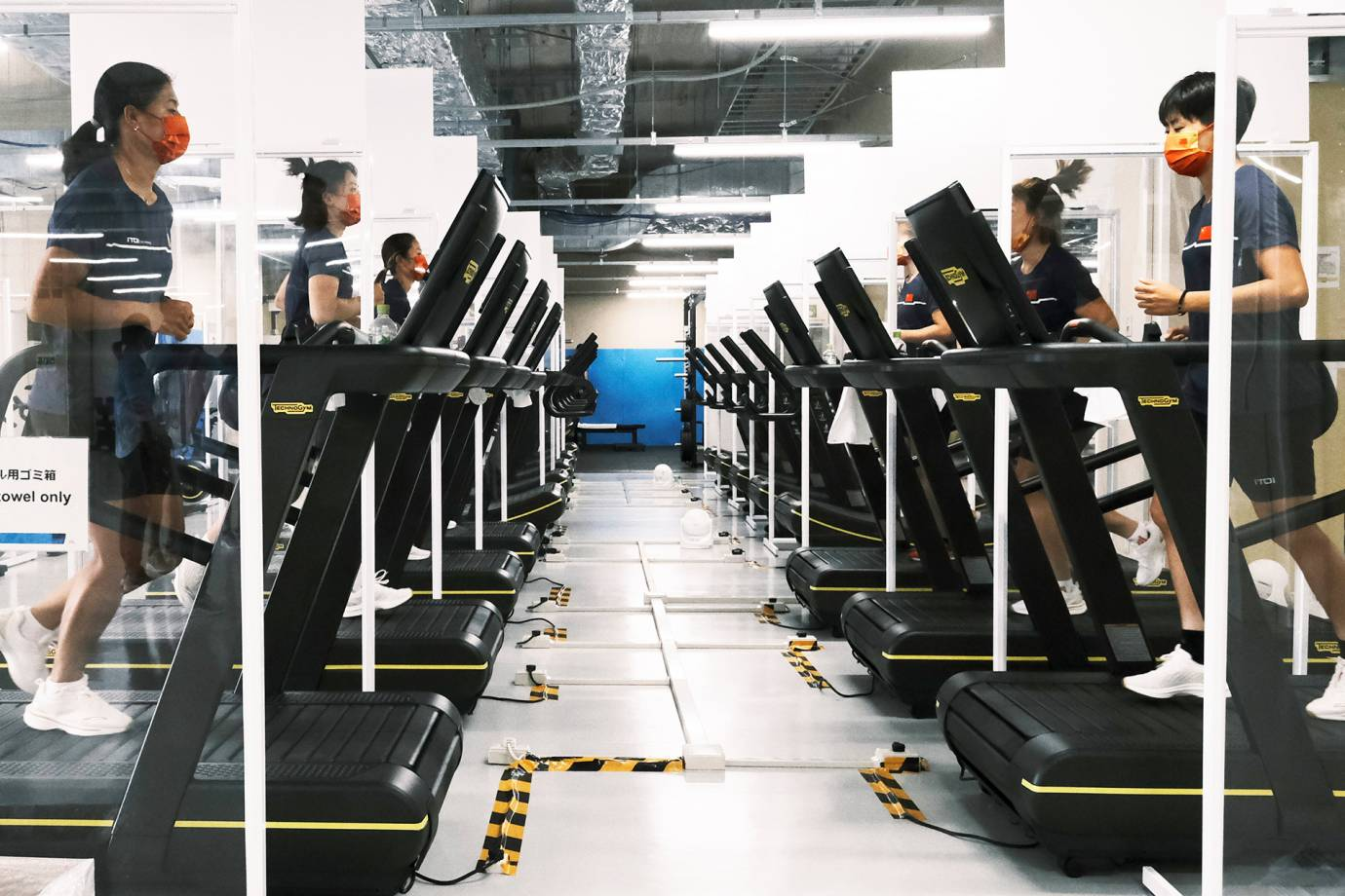 athletes on tradmills in the Olympic Village gym