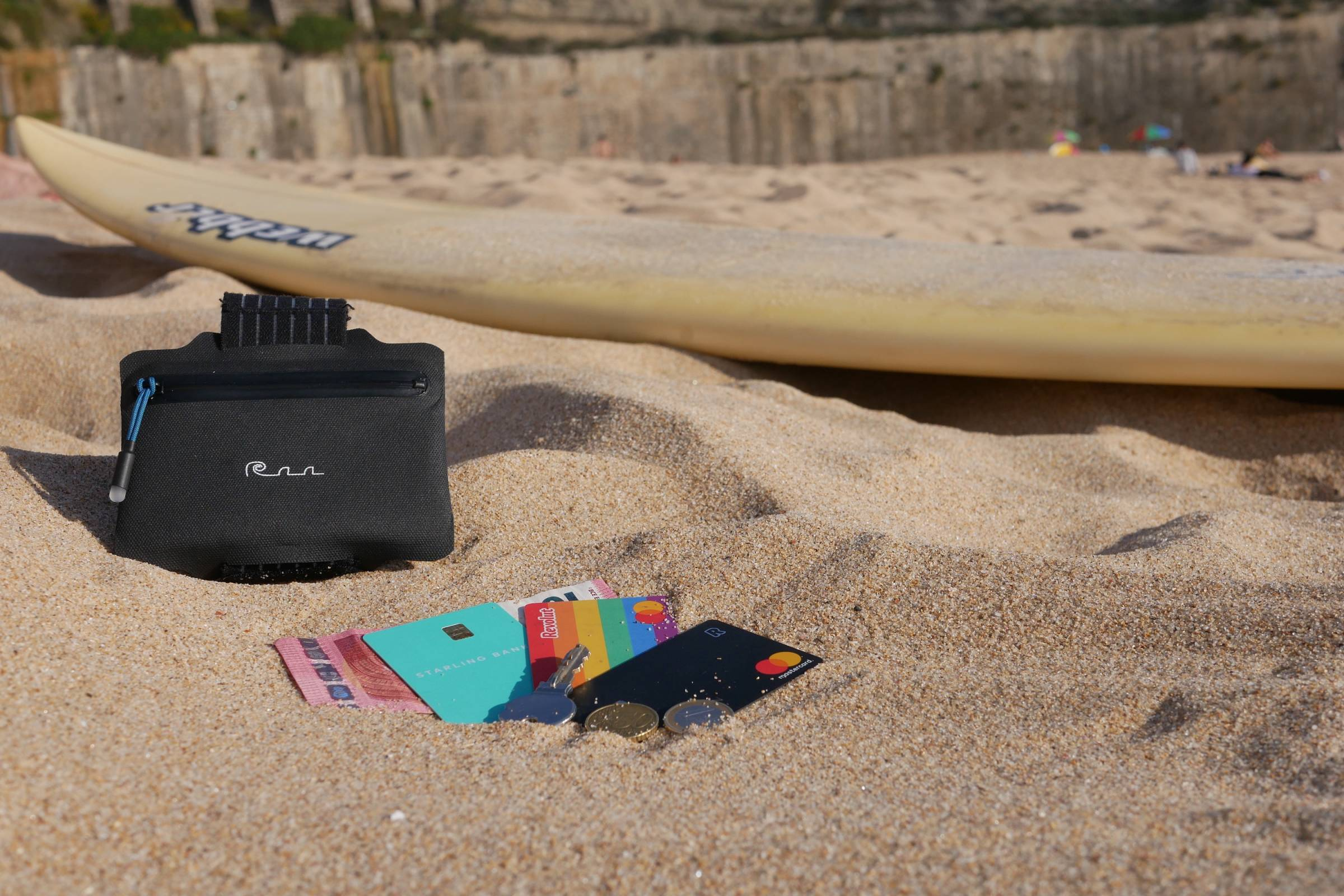 a waterproof wallet and fan of cards laid out on sandy beach