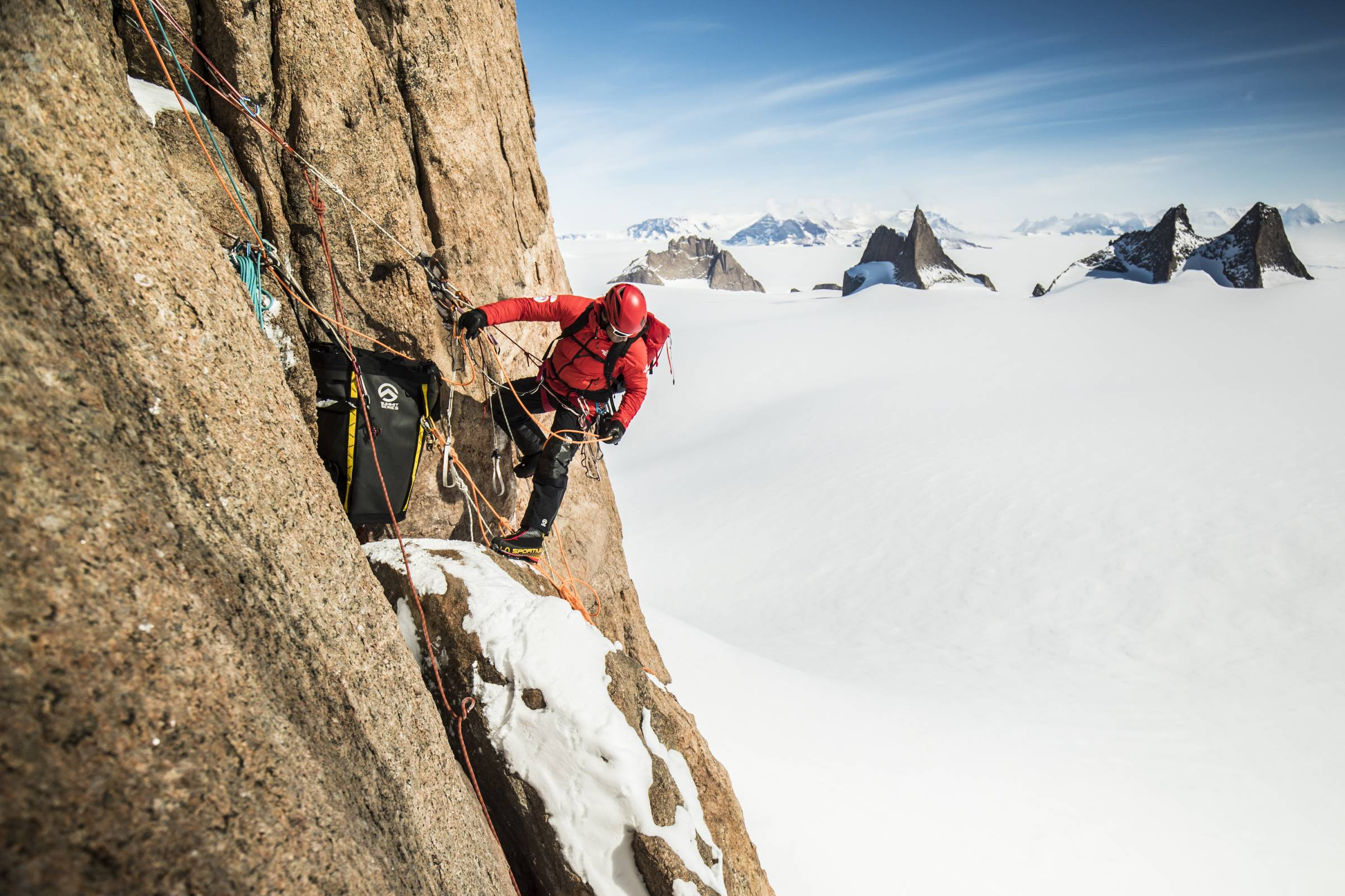 Cedar Wright in red puffy jacket climbing up face of peak in Antarctica