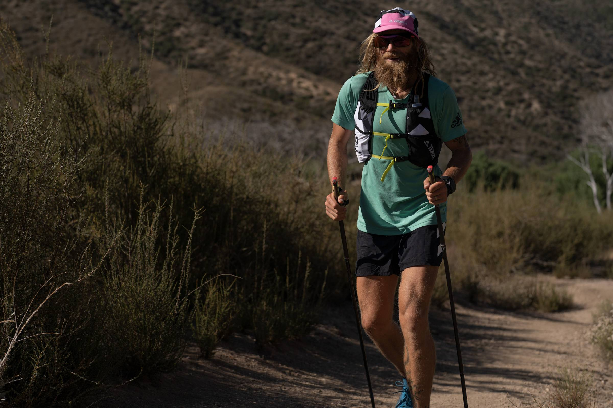 Timothy Olson running with trekking poles and a green shirt and pink hat on the Pacific Crest trail