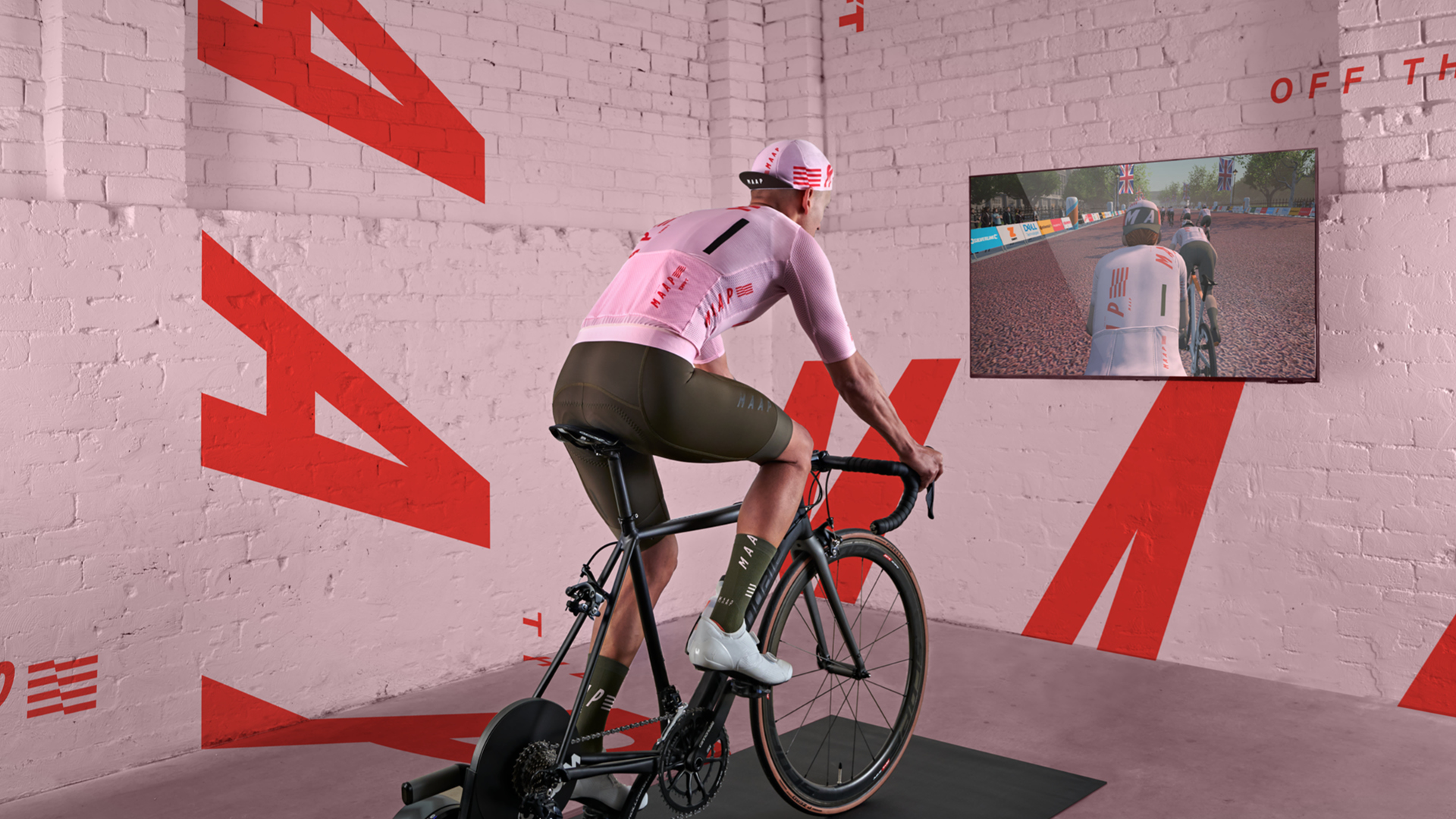 rider in a pink MAAP jersey and cap riding virtually in Zwift game