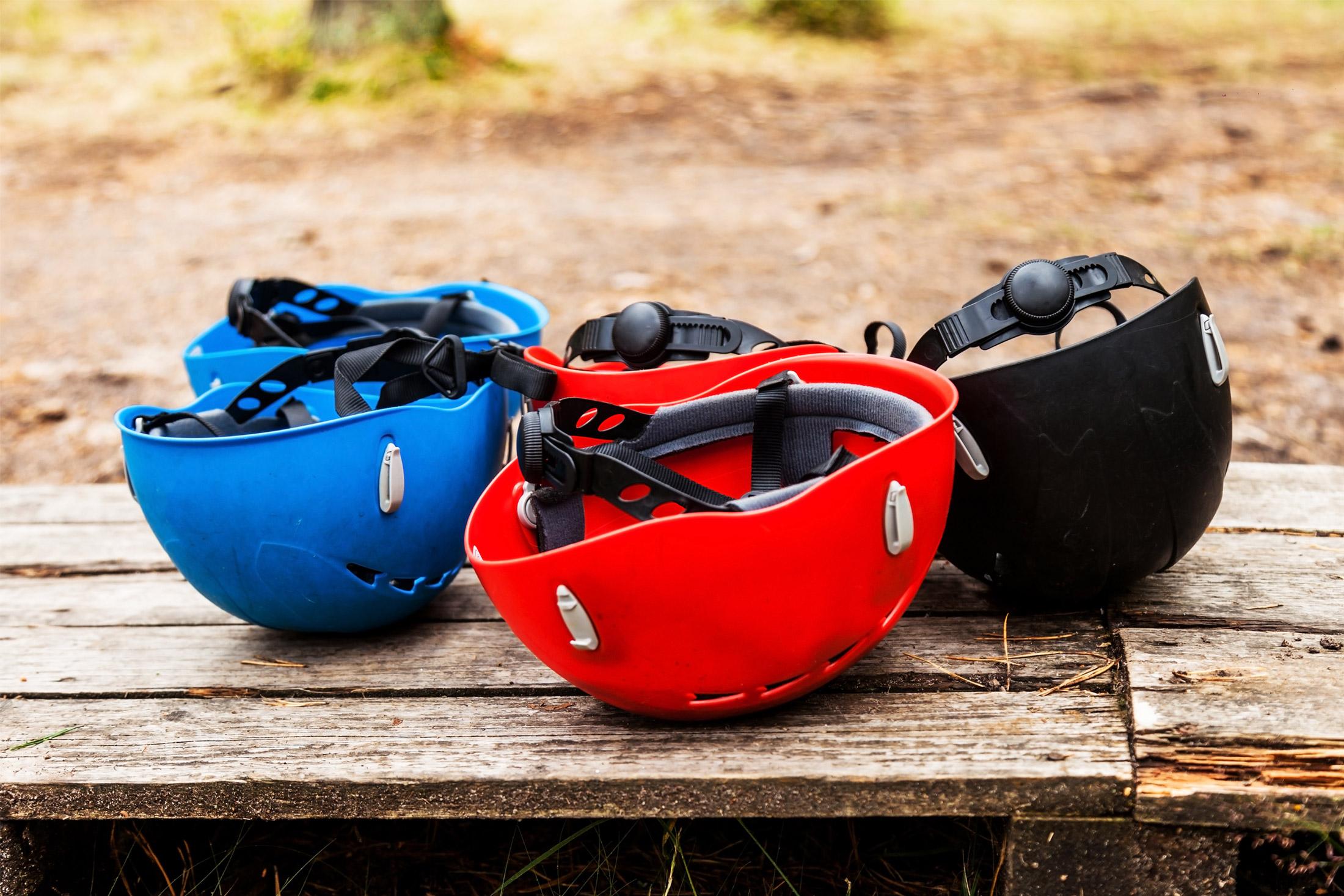 three climbing helmets sitting on a table
