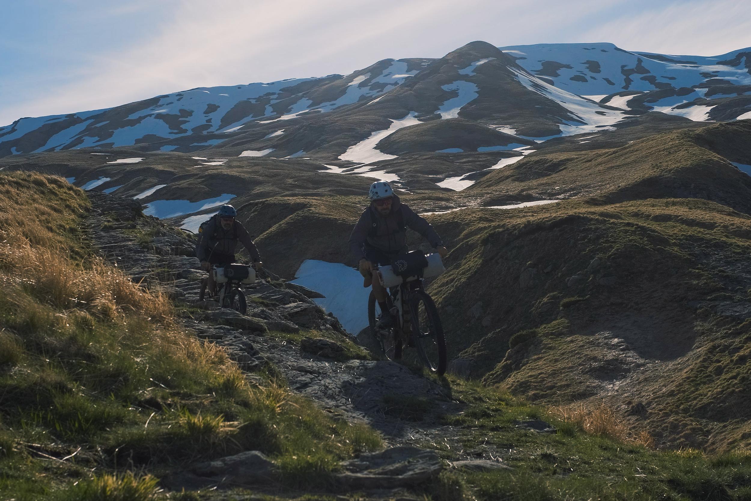 two guys mountain biking along singletrack trail in Italy on a high peak