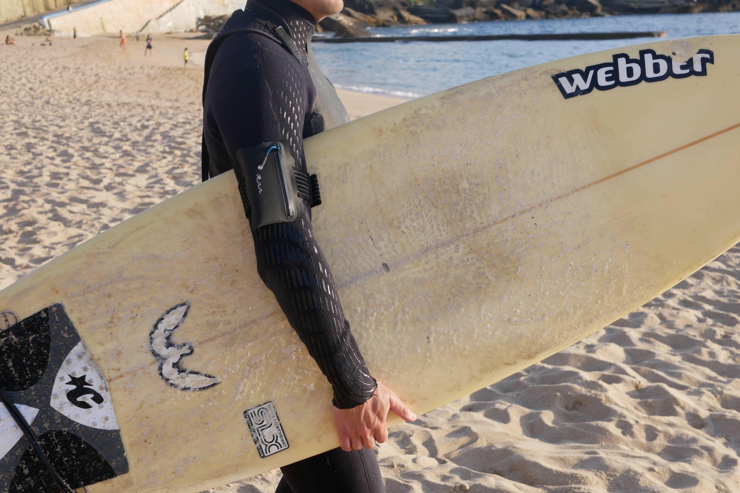 surfer wearing a submerge waterproof wallet armband
