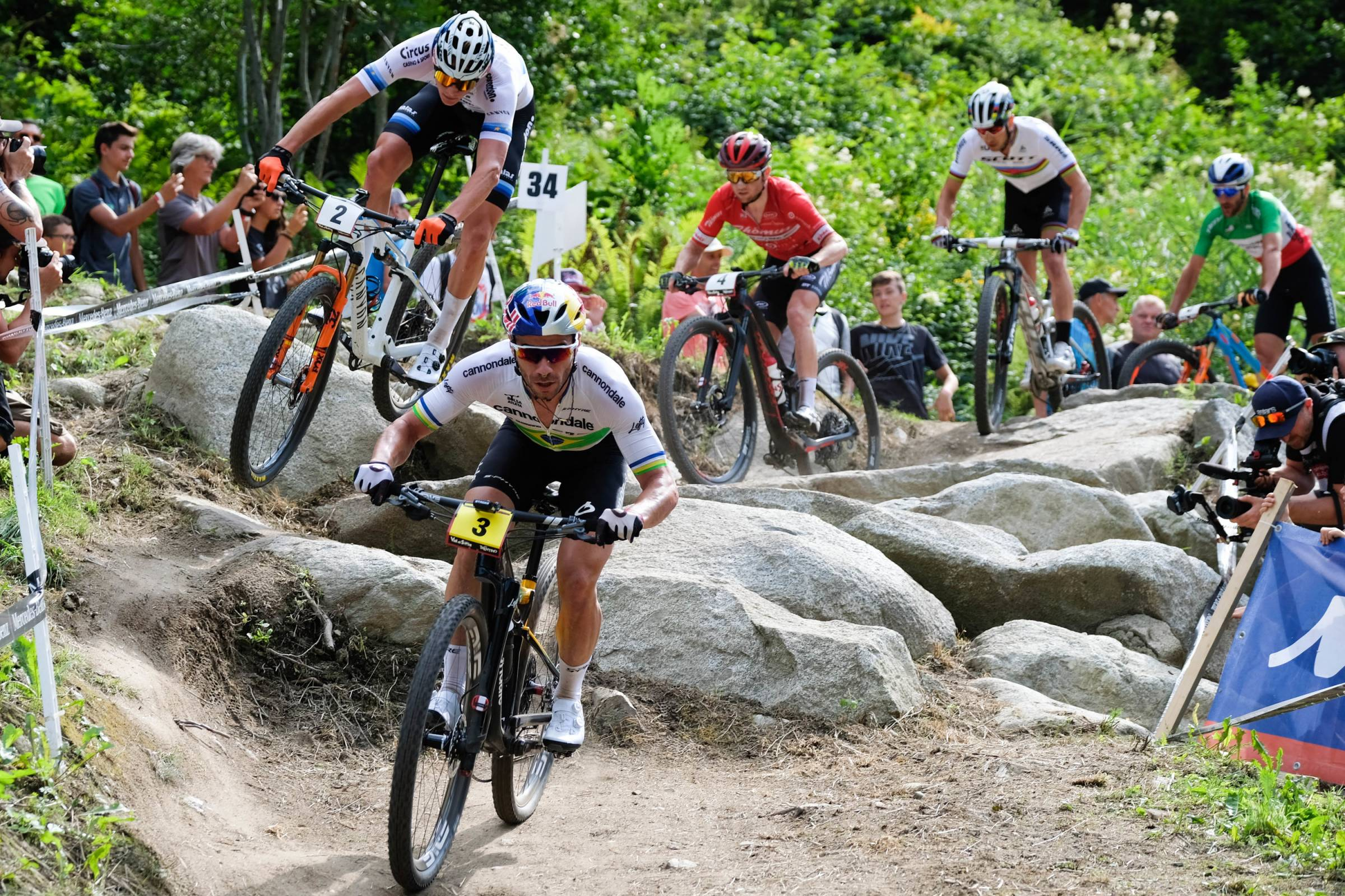 several mountain bike athletes racing down rocky course at a UCI World Cup